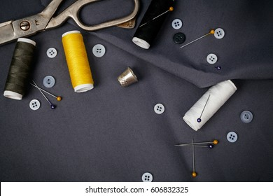 Sewing tools and sewing kit with thread coils and buttons on grey fabric background