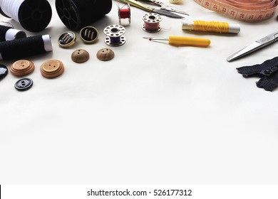 sewing tools on white fabric background. over light, retro tone and high contrast