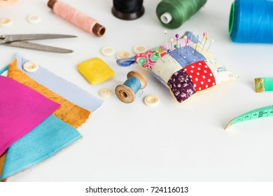 sewing tools, patchwork, tailoring and fashion concept - close-up on white work desk in studio, pincushion, thread spools, measuring meter, buttons, scissors, soap, pieces of colored patchwork fabric.