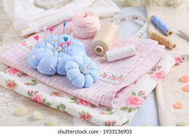 Sewing tools and supplies  - handmade pincushion, scissors, bobbins with thread, needles and fabric. Hobby, crafting, creativity, free time at home concept.