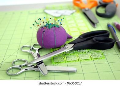 Sewing tools of the trade lay on a green cutting matt.  Pins are stuck in purple pin cushion and three pair of different sized scissors lay in a stack on table top.