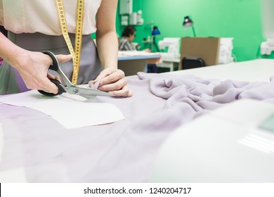 Sewing workshop. Seamstress at work. Marking and cutting fabric.