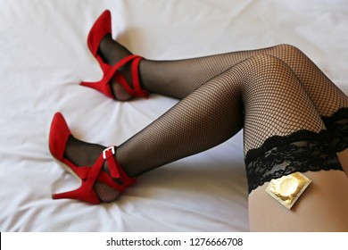 Sex with condom, seductive woman in black fishnet stockings on the bed. Safe sex concept, sexy female legs on high heels