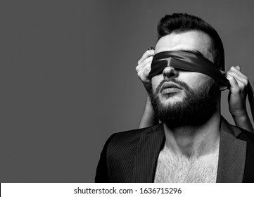 Sex game. Tease and seduce. Passionate lovers. Sex domination. Sex submission. Awakening his desire. Female tease guy. Macho well groomed bearded hipster tied eyes red ribbon. Sexual relations.
