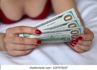 Sex for money, sexy woman in red lingerie lying in bed with US dollars in hands. Concept of prostitute, wages, savings