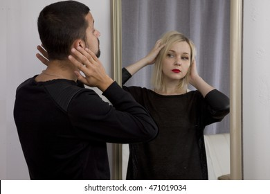 sex selection. man looks in the mirror and sees the reflection of a woman. straightens hair. gender identification
