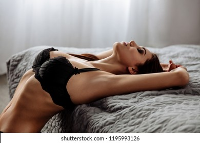 Sex. Temptation. Young slim woman in black bra is leaning sexually on bed