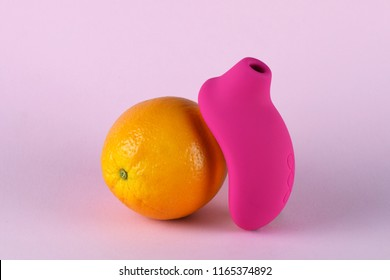 Sex toy for adult, design minimal dildo vibrator for clitoris isolated on pink background. Food minimal concept with orange.