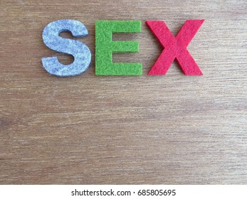 SEX word made from colorful felt fabric isolated on wood texture board.