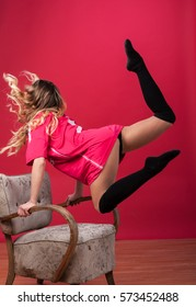 sexi girl jumping up above the armchair in room