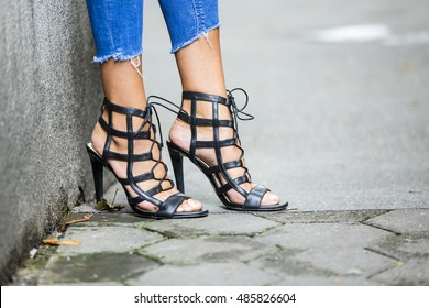 Sexi girl's legs wearing black sandals on the street