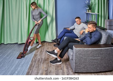 Sexism in the modern world, discrimination against women. Two men are sitting on the couch and watching how a slender woman with beautiful shapes does the cleaning of the apartment.