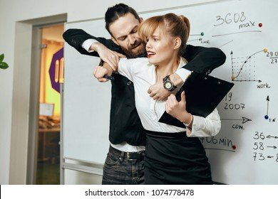 Sexual abuse and violence in the workplace. A boss aggressively grasping a young blonde employee from behind, starting to unbutton her blouse. The shocked and frightened girl struggling to break free.
