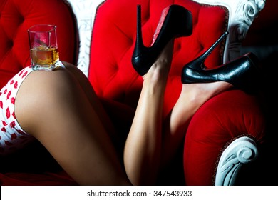 Sexual beautiful female buttocks and legs of young woman with straight slim flexible body in underwear with kiss print and high heeled shoes with glass of alcoholic beverage of brandy or whisky