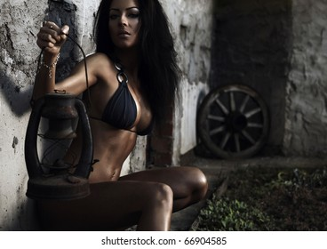 sexual beauty dressed in bikini poses sitting with oil lamp against an old stone wall.