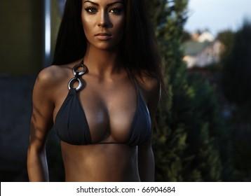 Sexual beauty dressed in bikini poses near building