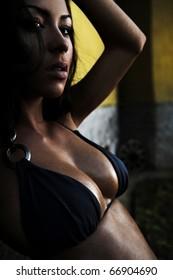 Sexual beauty dressed in bikini poses near old rock wall.
