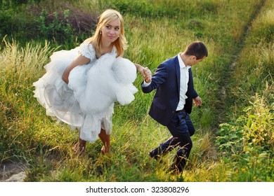 Sexual blonde bride and galant groom climbing down a hill