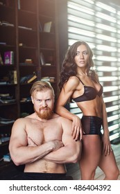Sexual bodybuilders. Portrait of a handsome man with a beard and a fitness woman.