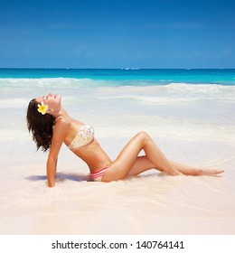 Sexual brunette girl take sunbath on the beach, happy female with frangipani flower in hair wearing stylish colorful swimwear, enjoying summer holidays