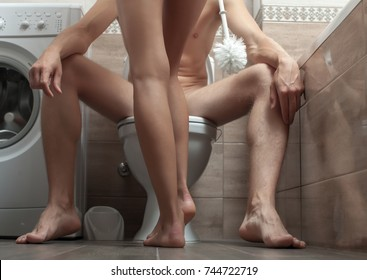 Sexual concept. Funny photo. Strong man. Toilet concept. Secret. Hot guy. Perfect legs man.Man is sitting on the toilet bowl. Holding paper in hands. Sexy couple. Man funny sitting. Erotic photo.