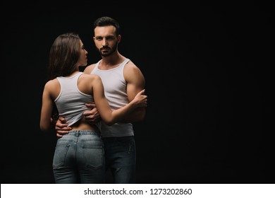 sexual couple in white singlets and jeans isolated on black