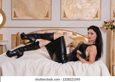 sexual cruel bdsm mistress wearing latex rubber outfit with fetish boots holds riding crop and posing in her golden bedroom