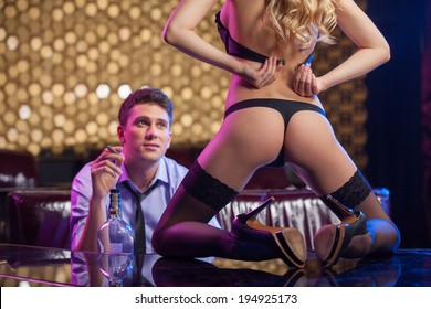 Sexual dancer taking off her bra. Man watching Sexy striptease in strip club