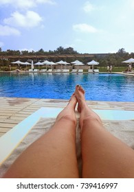 Sexual female legs against the background of the pool.
