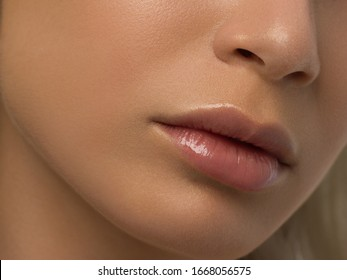 Sexual full lips. Natural gloss of lips and woman's skin. The mouth is closed. Increase in lips, cosmetology. Pink lips and long neck. Gentle pure skin and wavy blonde hair.