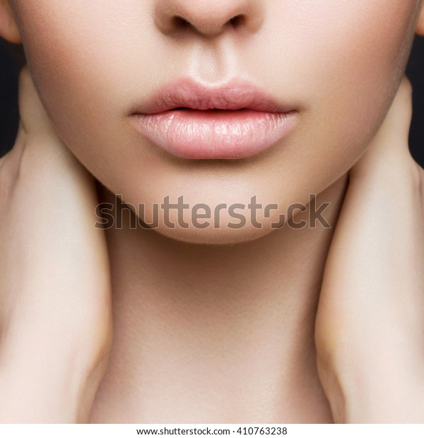 Sexual full lips. Natural gloss of lips and woman's skin. The mouth is closed. Increase in lips, cosmetology. Pink lips and long neck.