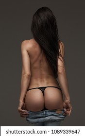 Sexual girl takes off her jeans. Seductive woman standing with her back to the camera and shows a beautiful ass, butt.