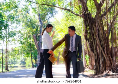 Sexual harassment concept: A businessman is touching businesswoman ass and beautiful working woman is slapping on his face at some park. The office girl looks nervous and shocked.