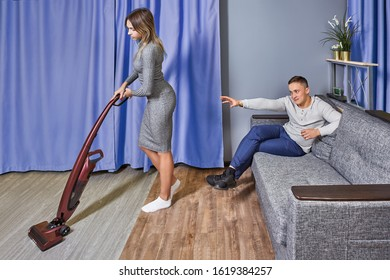 Sexual harassment and sexism towards a woman in workplace. A young man enjoys the work of an attractive maid and tries to touch her. Cleaning lady is vacuuming near the male who is sitting on couch.