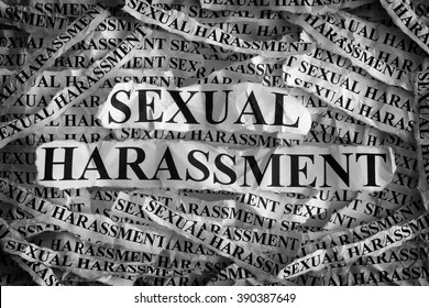 Sexual harassment. Torn pieces of paper with the words sexual harassment. Concept Image. Black and White. Closeup.