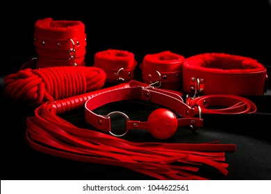 Sexual kink, erotic games and human sexuality concept with complete red sex toy kit set (ball gag, cuffs, rope, flogger, collar and leash) for BDSM fantasy play and bondge restraints on black silk