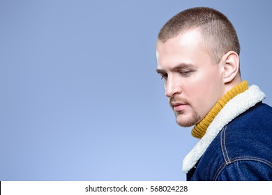 Sexual male model posing in jeans clothes. Short hair styling. Studio fashion shot.