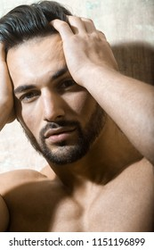 Sexual muscular nude man posing over white background. Man has headache, he holds his hands on head. Medecine from pain, painkillers. Sensual portrait of handsome guy's face. Trendy haircut.