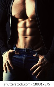 Sexual muscular young man over dark background.  Male torso, abdominals.