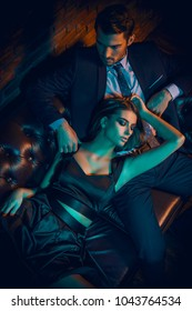Sexual passionate couple in elegant evening dresses. Fashion shot. Loft style interior.