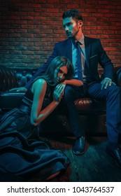 Sexual passionate couple in elegant evening dresses. Fashion shot. Loft style interior.