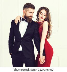 Sexual passionate couple in elegant evening clothes. Luxurious interior. Fashion shot. Woman feeling save in man's arms. Fashion photo of handsome elegant man in suit with beautiful sexy woman posing