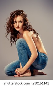 Sexual shirtless young woman alluring in jeans. Studio shot. Beauty, fashion.