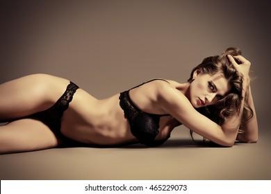 Sexual slim young woman in black underwear lying on the floor. Underwear fashion. Body, skin care.