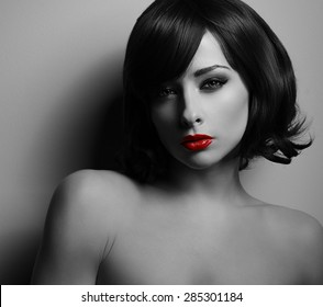 Sexual woman with black short hair and red lipstick looking on dark background with shadows