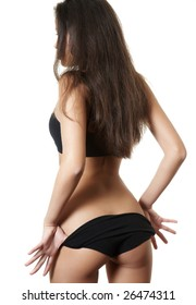 sexual woman in black underwear stands by a back and take off  panties