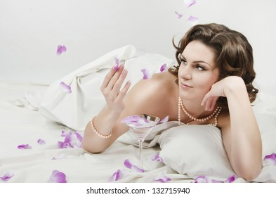 Sexual woman lying in bed on white sheets