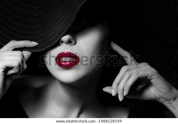 Sexual woman with red lips in black hat. Close-up high fashion portrait. Mysterious black and white image. Sensuality. Sexuality. Femme Fatale style.