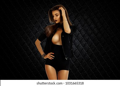 Sexual young brunette girl with big breast in studio on black background