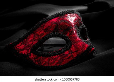 Sexuallity, sensuality and eroticism concept with close up on a beautiful red lace masquerade vintage gothic mask on black silk